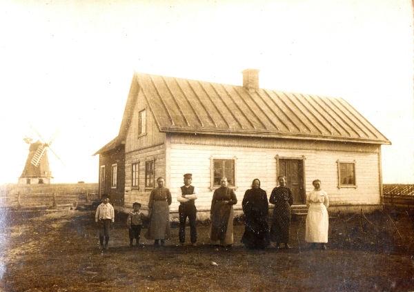 """Gamla Smiss 616: från vänster Olof Larsson, född 1910, senare ägare till Hallbjänne 504; Lennart Larsson, född 1913, och senare mejerist i Stånga; söner till Anna Häglund, född 1872 på Alvare 435; och Johannes Larsson, född 1864; okänd; Birgitta """"Briten"""" Holmér, född 1845 i holmvaktarbostaden på Närsholm gift Nilsson Närsholm; okänd; Ester Larsson, född 1895, och dotter till Anna och Johannes och gift till Fie i Lau"""
