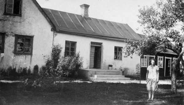 Alfhild Salmberg, född 1906, och 1931 gift med Ragnar Jakobsson, framför boningshuset på Haltarve 213. Alfhild bodde kvar i huset till sin död 1978. I dag ägs huset av Maj Bergström och Karl-Inge Siggelin.