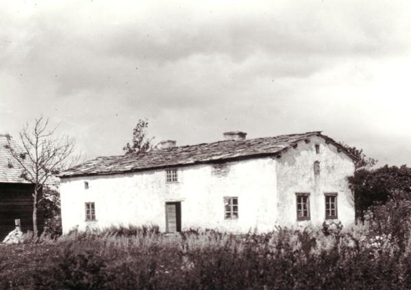 På baksidan av fotot står Mickels När. Det är oklart var det vackra huset låg. En teori är att det kan vara Mickel-Sunes gamla hus, Mickels 329, som låg mellan Mickels-Olles och ridskolans hus innan boplatsen efter laga-skiftet fick flytta till sin nuvarande plats.