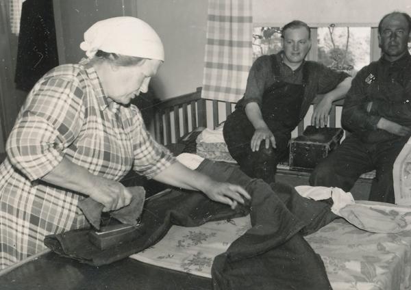Smiss 523: Emelie Dahlqvist, född Pettersson i Burs, stryker byxor medan Karl-Erik Lindberg Folke 529, född 1923, och Emelies son Gustav Dahlqvist, född 1925, tittar på.