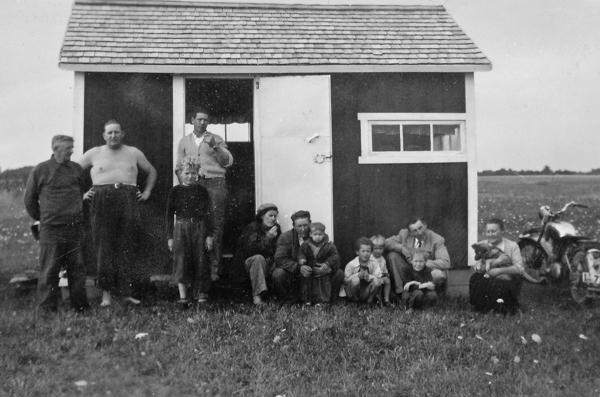Stuga via Austerveiki: från vänster Oskar – Klockar Oskar – Jakobsson Hallute 146, född 1892 vid Dalbo AJ; sonen Hans Dunstrand, född 1921; Oskars dotterson Eddy Olsson, född 1944 och gift i Lau; bakom honom Eddys pappa Ivar Olsson, född 1924 i Rone; Wilma gift med Oskars son Arne Dunstrand, född 1927 och gift i Klinte; med sonen Eilert; Eddys bröder Johnny, född 1948 och bosatt i Visby men med fritidshus i När; Tom, född 1951 och Sten, född 1945 och bosatt i Mickelgårds 363; bakom pojkarna Hans och Arnes bror Gösta Dunstrand, född 1919 och gift i Lau: och längst till höger Oskars hustru Agda Jakobsson, född Pettersson 1897, med familjens hund Seppi.