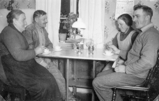 Kaffestund på Folke 849; till vänster sitter vid fönstret Johan Alkvist (1866), född vid Allmunde; och hans hustru Hilma Alkvist (1864), född Nilsdotter vid Husarve; på andra sidan bordet sonen Ragnar Alkvist (1904) och hans hustru Anna Alkvist (1907), fdd Nilsson vid Matisse 247.