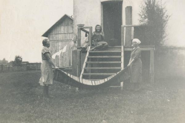 Annie Larsson Smiss 602, född Hallqvist år 1918 vid Pavals 308; och Hilda Olsson Mickelgårds 177, född 1896, ruskar mattor efter Greta och Axel Häglund Bomunds i Hammarens bröllop 1945 medan Gretas syster Sigrid Pettersson Maldes 330, född 1929 och senare gift Burs, tittar på