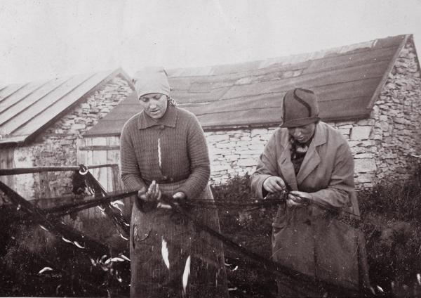 Från vänster Ella Pettersson Maldes 330, född Larsson vid Frigges 342 år 1904, mormor till Carina Thorén, och Sally rensar nät.