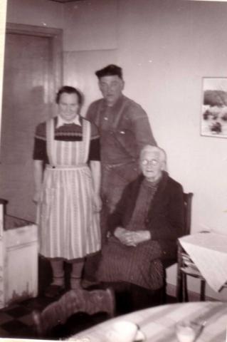I köket på Hallbjänne 680: Stående Annie Nilsson, född Johansson år 1913 vid Haltarve 219 med sin man Axel Nilsson född 1908. Sittande Axels mor Hulda Nilsson född Johansdotter år 1873 Mickelgårds 393.