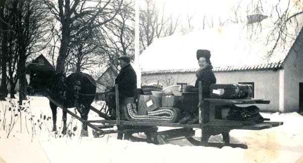 """Flyttlass med släde: på kuskbocken """"Klockar Oskar"""" Jakobsson Hallute 146, född 1892, med passagerare som kan vara en piga som arbetat i prästgården."""