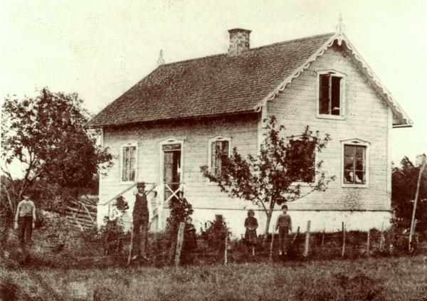 Hallute 115 där Lennart och Riitta Olsson bor idag. Huset byggdes på Hallute gräsänge av Lennarts farfar Lars Olsson som var skräddare och syns mitt i bilden. Han föddes 1856 vid Gangvide 505. Familjen hade åtta barn och pojken till höger är Lennarts far Oskar Olsson, född 1890, som tog över yrket som skräddare.