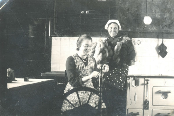 Stående Hermanna Dahlgren Kulle 862, född 1909, och pigan Elsa Olsson Öndarve 873, född 1920, vid spinnrocken