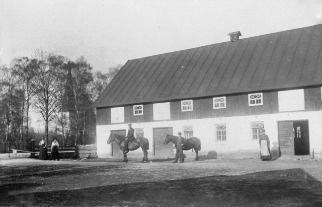 Ladugården vid Hägdarve 403 HP. På hästen sitter Henrik Pettersson (1899-1991), Torsten Henrikssons far. Med den andra hästen hans far Hjalmar Pettersson (1871-1964) och längst till höger Hjalmars fru Hulda Pettersson (1870-1963), Ingmansson i Hemse. De tvåkvinnorna längst till vänster är okända.